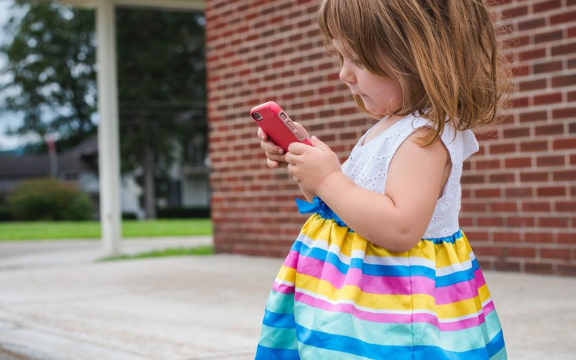Toddler girl looking at smart phone